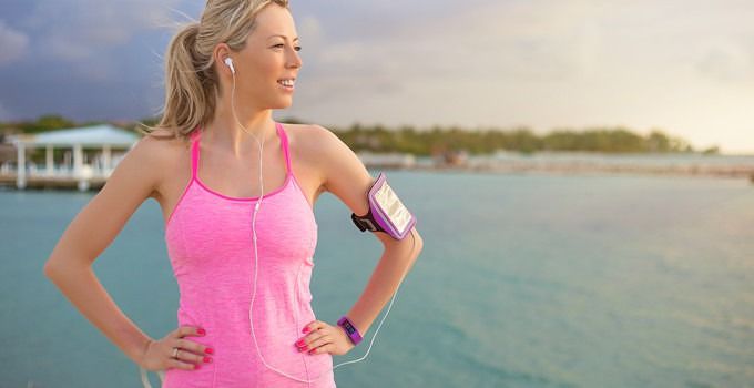 Pretty blonde women standing on beach in exercize clothes with iPhone