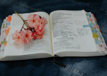 Open bible with handwritten notes and flowers on top