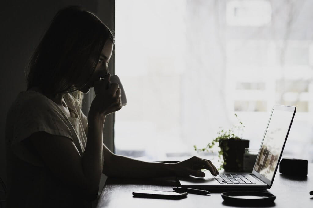 Woman drinking coffee learning how to choose a VPN on her laptop