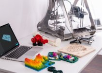 3D printer on desk next to laptop, creations