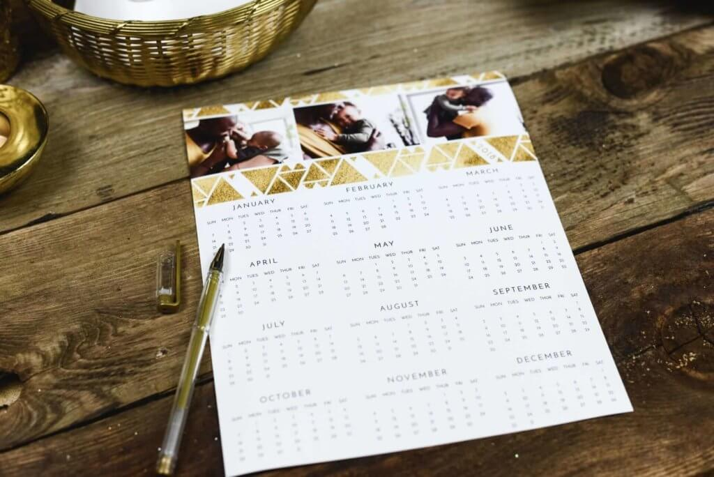 black pen near a calendar on a table