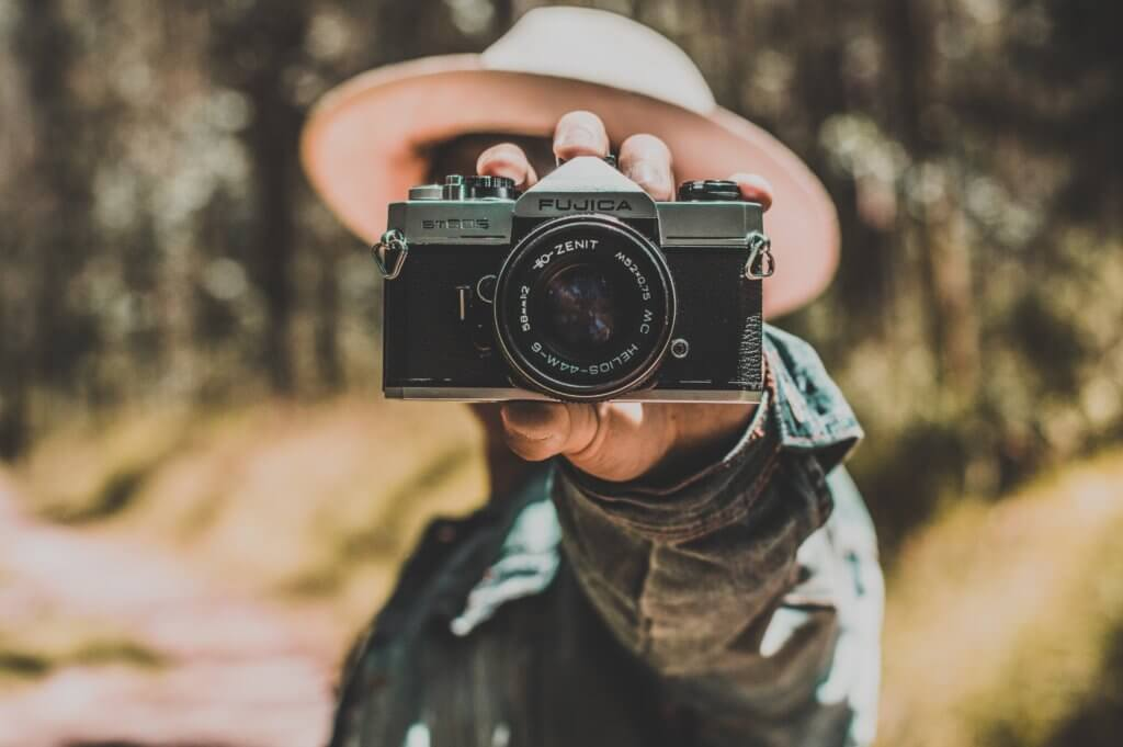 person holding black and silver camera doing a reverse image search for duplicate image online