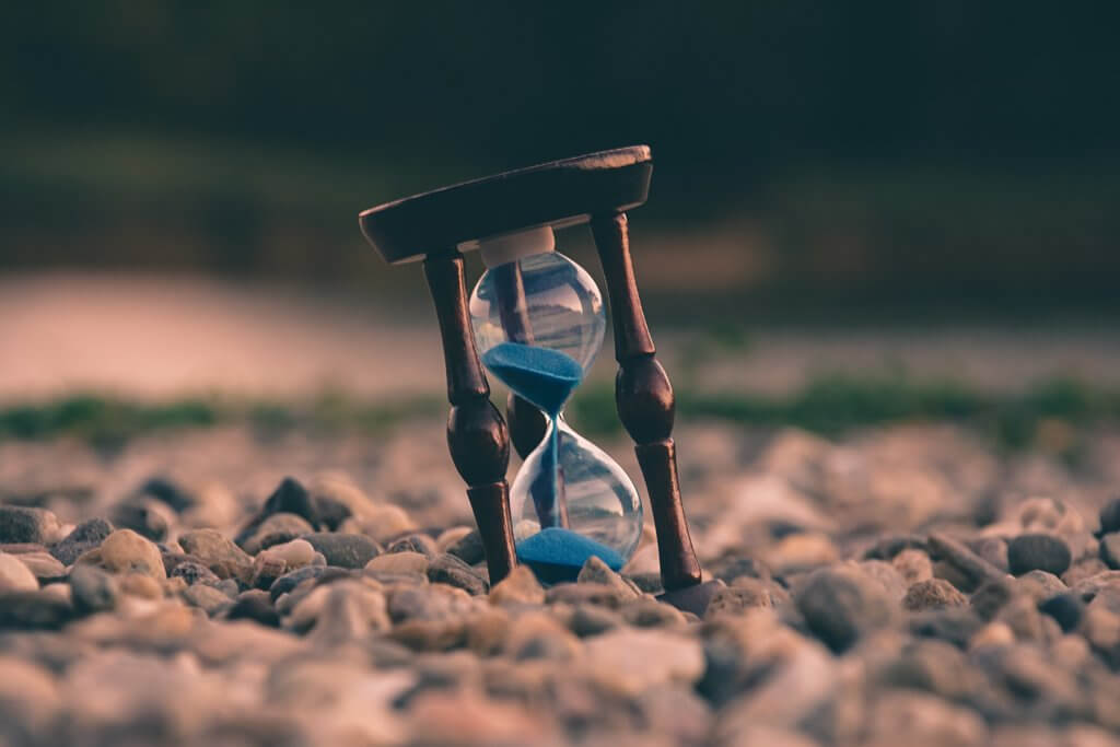 Hourglass with blue sand on rocks - track productivity with iOS apps