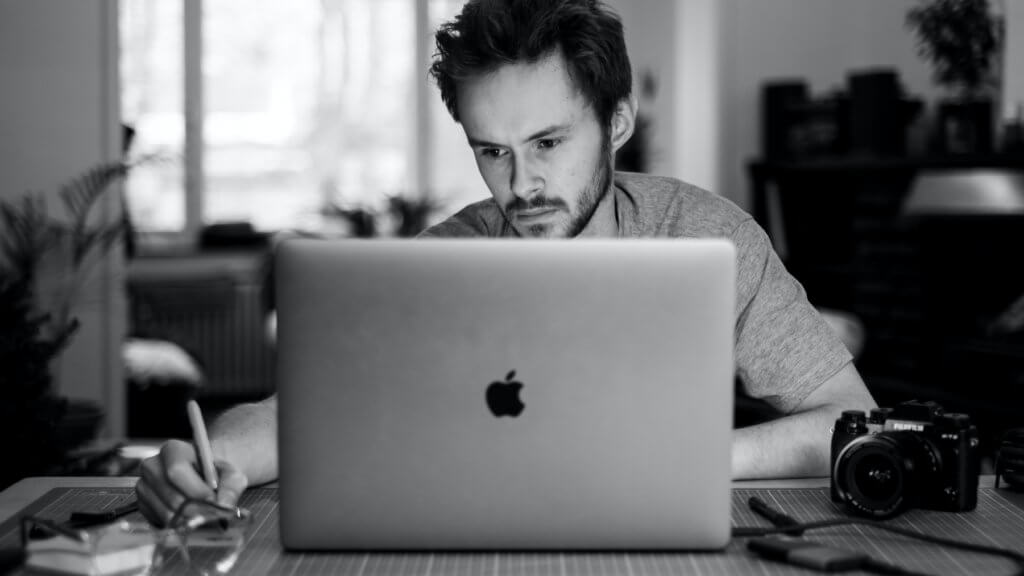 man using business management software on his MacBook to run his freelance business - Photo by Jonas Leupe