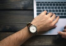 person wearing brown and white watch waiting for MacBook
