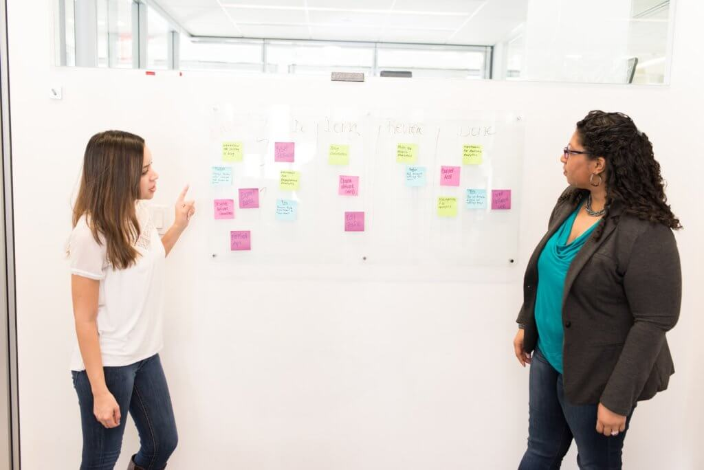 two women standing beside white board discussing test suites