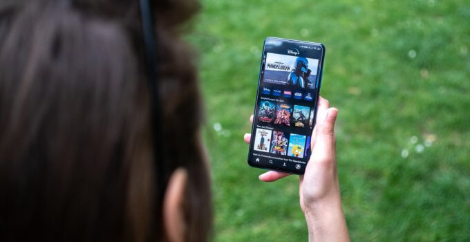 woman holding black android smartphone watching videos