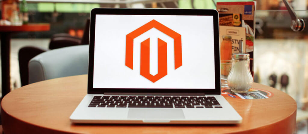 Macbook on a table showing the Magento logo