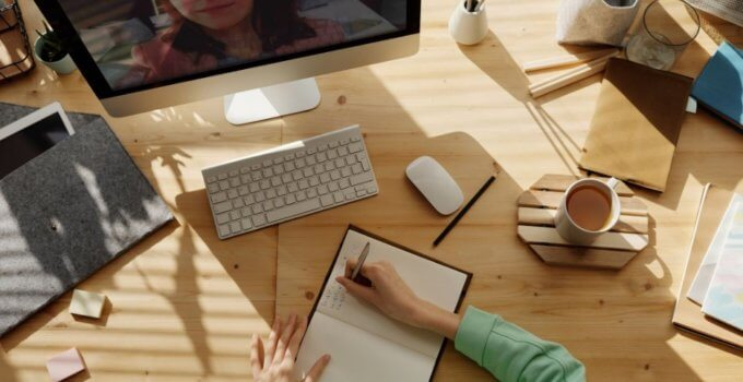 Woman writing in journal on desk with Mac