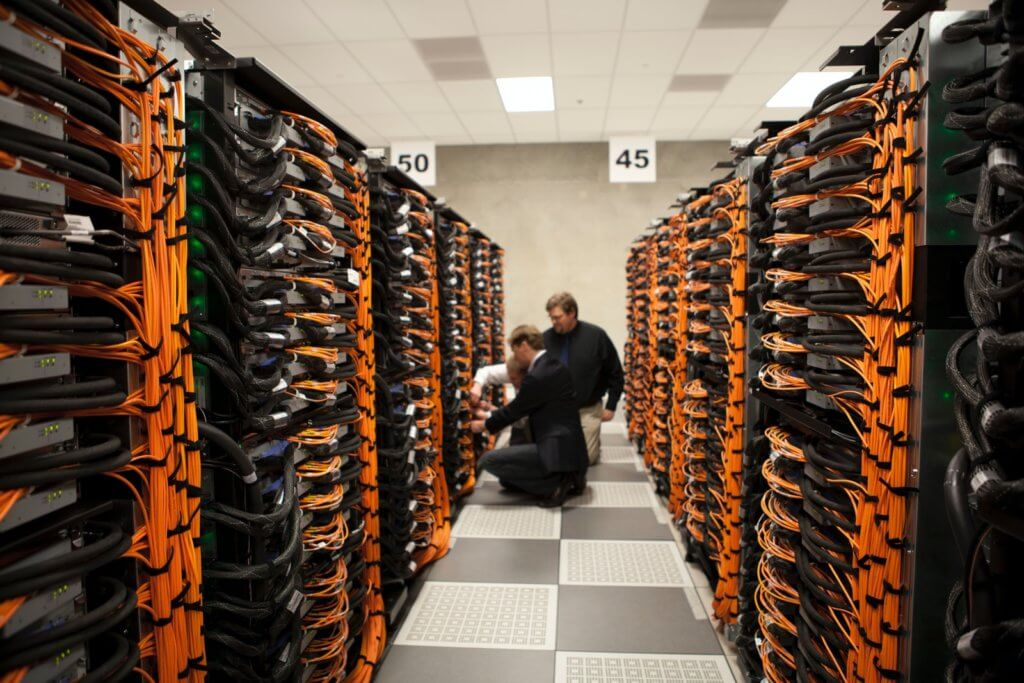 three men working on VPS servers in server room with lots of orange cables